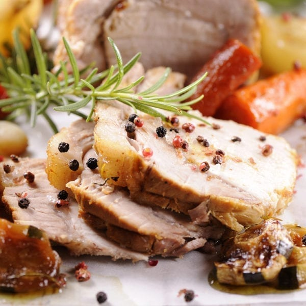Pork slices on a white plate with potatoes and carrots, garnished with rosemary.