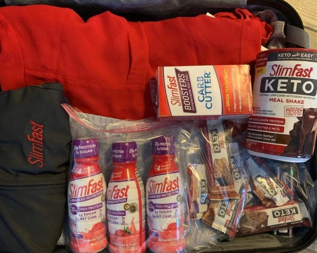 SlimFast RTD Shakes, Keto Meal Replacement Bars, Keto Meal Replacement Powder, and SlimFast Boosters in a suitcase